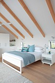 White, high-ceilinged attic bedroom