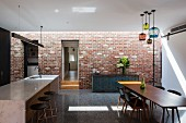Industrial-style kitchen and dining room with brick wall