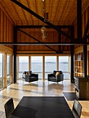Modern wooden house with glass wall, black girders and black furniture