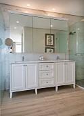 Weißes Waschtischmöbel vor Marmorwand und Spiegelschrank