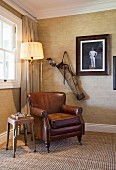Brown leather armchair and standard lamp below vintage photo and golf bag in corner