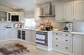 Gas cooker, stainless steel extractor hood and animal-skin rug on tiled floor in white country-house-style kitchen