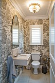 White WC, cistern and sink in guest toilet with patterned wallpaper