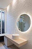Round mirror on white structured wall tiles in minimalist bathroom