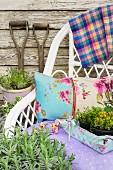 Weisser Korbstuhl mit Kissen und Stofftablett mit frischen Kräutern an Holzwand im Garten