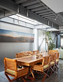 Wooden table, wicker chairs and steel structure in dining area