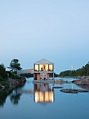 Illuminated floating wooden house at twilight