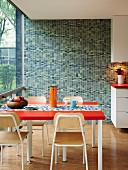Mosaic wall in various shades of green in retro kitchen with glass wall