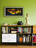 Books on sideboard with white drawers and shelves below framed artwork on light green wall