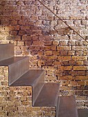 Close-up of self-supporting sheet-steel staircase against restored brick wall