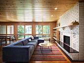 Lange, blaue Couch vor offenem Kamin in heller Ziegelwand