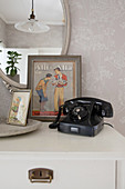 Old black telephone and vintage pictures on chest of drawers