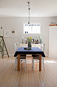 Bright dining room in simple country-house style with wooden floor