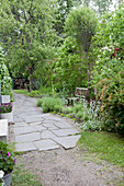 Irregular, stone-flagged path in lush garden