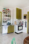 Retro-Küche mit olivgrünen Fronten, altem Herd und Wandregalen