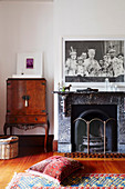 Antique bar cabinet and fireplace with large black and white photo in the living room