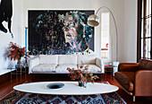 Klassiker, ovaler Couchtisch, Couches, Bogenlampe und großformatiges Gemälde im Wohnzimmer