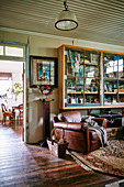 Display cabinet on the wall and vintage leather armchairs in a converted stable