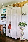 Weisser Kleiderschrank neben Antik Pflanzengefäss aus Porzellan
