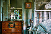 Antique chest of drawers next to metal bed in vintage bedroom with corrugated iron wall