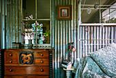 Antik Kommode neben Metallbett in Vintage Schlafzimmer mit Wellblechwand