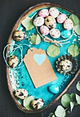 Colorful quail eggs, dried flowers and leaves for Easter holiday over turquoise blue tray with craft paper label