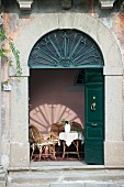 Traditional arched entrance with open, dark-green double doors