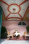 Einblick auf Loungebereich mit Rattanmöbeln und künstlerischer Deckengestaltung