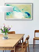 Wooden dining table and wood and cane chairs in front of modern painting