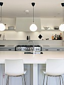 White counter with sink and bar stools in white kitchen with various lighting