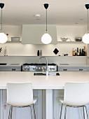 Beleuchtete, weisse Küche mit Küchentheke, Spüle und Barhockern