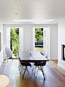 Classic chairs in elegant dining area with exotic-wood parquet floor and view of summery garden