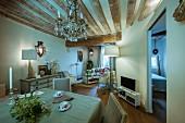 Offener Wohnraum in restaurierter Altbauwohnung mit rustikaler Holzbalkendecke, Kronleuchter und antiken Möbeln