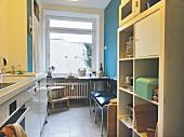 Küche mit Küchenzeile und offenem Regal, im Hintergrund Essplatz vor dem Fenster