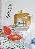 A bureau attached to the wall and a red designer chair in a bedroom
