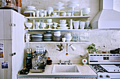 Fully loaded crockery shelf over sink in vintage kitchen