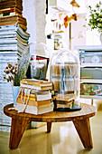 Holzhocker mit Büchern und Glashauben
