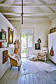 Sessel, Holzschrank, Schneiderpuppen, Goldrahmen-Bilder im Zimmer mit Tür zum Garten