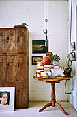 Antique wooden table with books next to vintage metal cupboard in living room with white painted brick wall