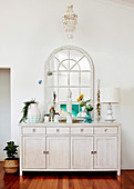 White chest of drawers with decorative objects and arched mirror