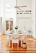 Laid dining table with white wooden chairs under ceiling fan