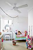Weisses Kinderzimmer mit bunten Accessoires, Mädchen liegt mit Buch auf Bett