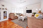Polstergarnitur und rollbarer Palettentisch im Wohnraum mit weiss gestrichener Holzwand