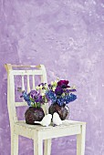 Flowers in red cabbages used as vases and white bird figurines on vintage wooden chair