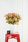 Flowers in glass vase covered in paper with graphic pattern arranged on red stool