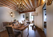 Chandelier and rustic wood-beamed ceiling in dining area with historical ambiance