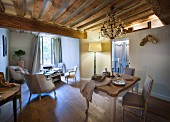 Lit standard lamp and rustic wood-beamed ceiling in dining area with historical ambiance