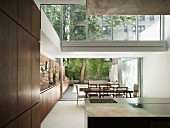 View from open-plan kitchen to dining area and terrace with continuous sideboard leading along one wall to outdoor kitchen