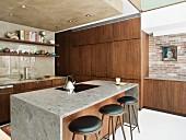 Kücheninsel mit filigranen Barhockern und Einbauschränke mit Edelholzfronten neben restaurierter Ziegelwand