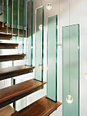 Stair treads with separate glass balustrade panels in front of several spherical pendant lamps